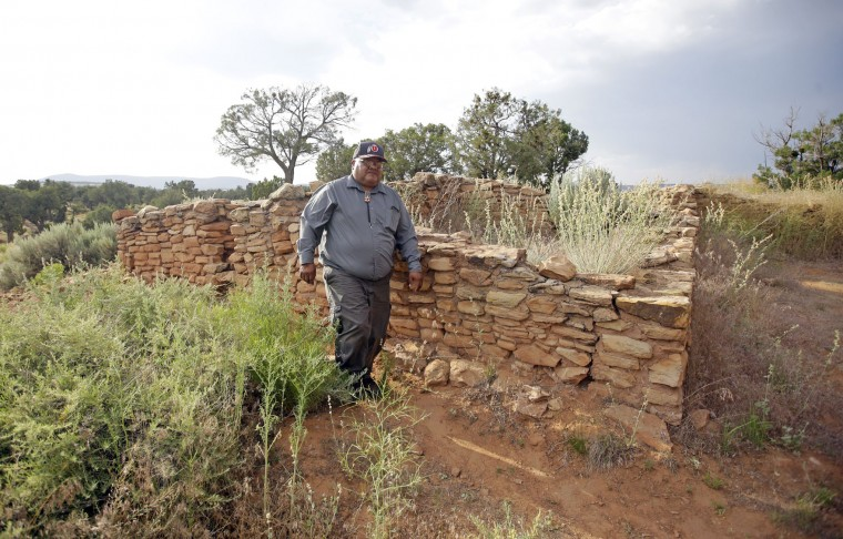 "This June 21, 2016, photo, Malcolm Lehi, a Ute Mountain Tribal Commissioner walks pass the Mule Canyon ruin, near Blanding, Utah. ""We don't want to forget about our ancestors,"" said Lehi. ""Through them we speak. That's the whole concept of protecting and healing this land. They are still here among us as the wind blows."" (AP Photo/Rick Bowmer)"
