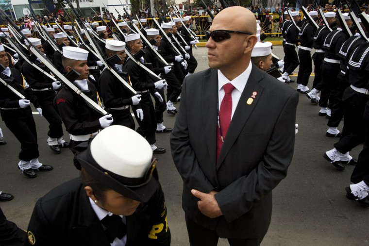 A security officer stands guard as navy forces march in a military parade to mark the country's Independence Day in Lima, Peru, Friday, July 29, 2016. Peru declared it's independence from Spain on July 28, 1821. (AP Photo/Rodrigo Abd)