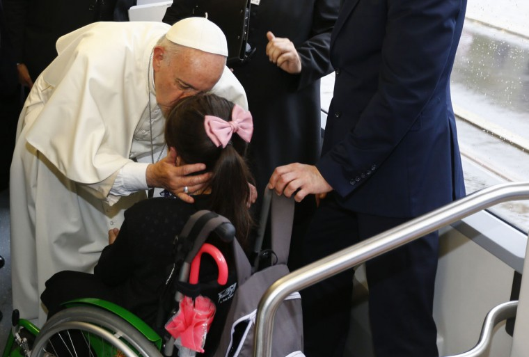 Pope Francis kisses a girl during his tram journey to Krakow's Jordan Park, Poland, during the World Youth Days. (Stefano Rellandini/Pool Photo via AP)
