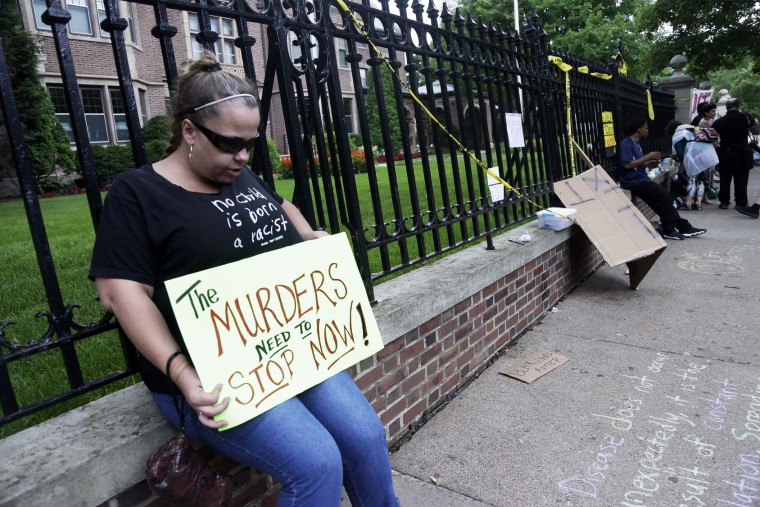 Sara Trok sits alone with her sign as demonstrators gather outside the governor's residence Friday, July 8, 2016, in St. Paul, Minn. , where protests continue over the shooting death by police of Philando Castile after a traffic stop Wednesday, July 6, in Falcon Heights. (AP Photo/Jim Mone)
