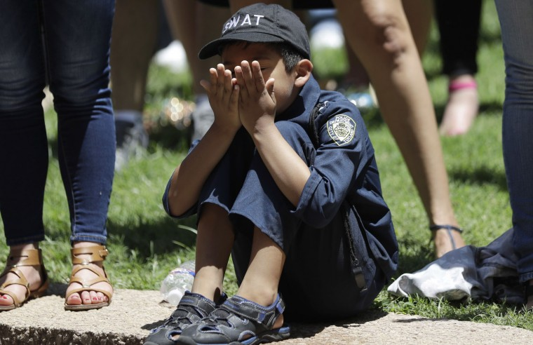 A young boy wears a police uniform as he takes part in a prayer vigil at Thanksgiving Square, Friday, July 8, 2016, in Dallas. Five police officers are dead and several injured following a shooting during what began as a peaceful protest in the city the night before. (AP Photo/Eric Gay)