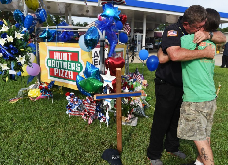 New Jersey Police Chaplain Bob Ossler, left, hugs Matthew Saia, right, after a prayer at a makeshift memorial in Baton Rouge, Monday, July 18, 2016. Multiple police officers were killed and wounded Sunday in a shooting near a gas station in Baton Rouge, less than two weeks after a black man was shot and killed by police, sparking nightly protests across the city. (Henrietta Wildsmith/The Shreveport Times via AP)