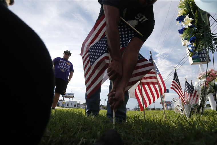 A man plants American flags at a makeshift memorial at the scene of the shooting of police officers, in Baton Rouge, Monday, July 18, 2016. Multiple police officers were killed and wounded Sunday morning in a shooting near a gas station in Baton Rouge, less than two weeks after a black man was shot and killed by police here, sparking nightly protests across the city. (AP Photo/Gerald Herbert)