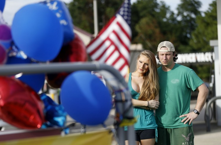 Brandon Howell and Lacey Cullen look at a makeshift memorial after placing flowers, at the scene of the shooting of police officers, in Baton Rouge, Monday, July 18, 2016. Multiple police officers were killed and wounded Sunday morning in a shooting near a gas station in Baton Rouge, less than two weeks after a black man was shot and killed by police here, sparking nightly protests across the city. (AP Photo/Gerald Herbert)
