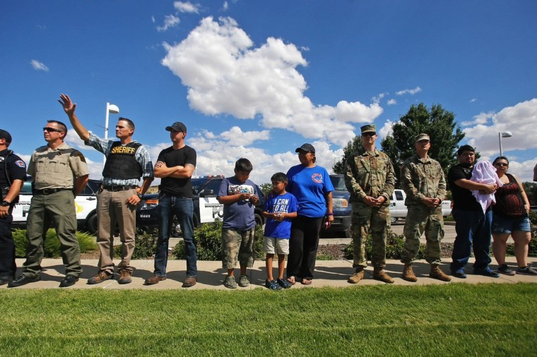 In this Monday, July 18, 2016 photo, community members and local law enforcement officers line up on outside the Farmington, N.M., Museum at Gateway Park for a moment of silence in honor of the officers injured and killed on Sunday in Baton Rouge, La. (Jon Austria/The Daily Times via AP)