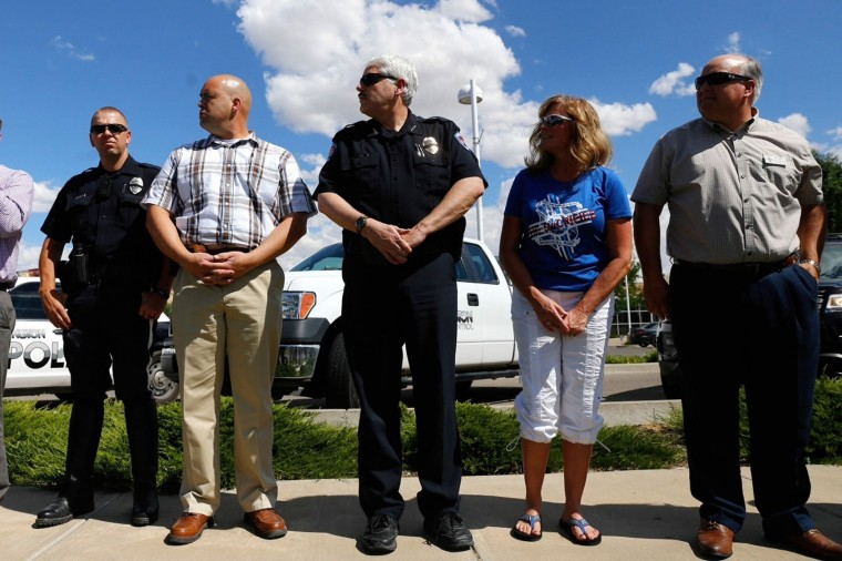 In this Monday, July 18, 2016 photo, Farmington Police Chief Steve Hebbe, center, participates in a moment of silence, in front of the Farmington Museum at Gateway Park in Farmington, N.M.(Jon Austria/The Daily Times via AP)
