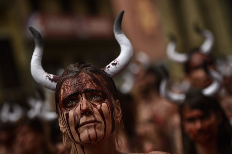 A woman with her face covered by theatrical blood takes part in a protest against bull runs in front of the City Hall on the eve of the famous San Fermin festival, in Pamplona, northern Spain, Tuesday, July 5, 2016. The festival will begin on July 6 with the ''txupinazo'' opening ceremony, with people participating in bull runs, music and dance, through the old city. (AP Photo/Alvaro Barrientos)