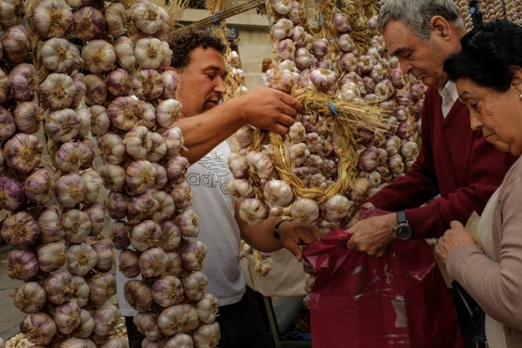 People buy some strips of garlic during the garlic fair in Vitoria, northern Spain, on Monday. (Alvaro Barrientos/AP)