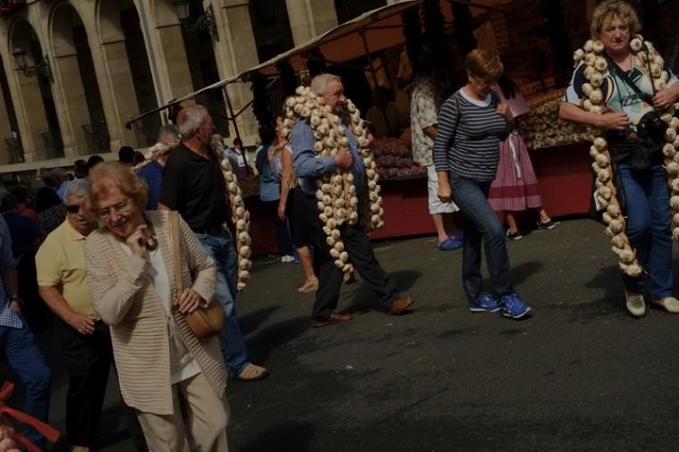 People carry strips of garlic during the garlic fair in Vitoria, northern Spain, on Monday. (Alvaro Barrientos/AP)