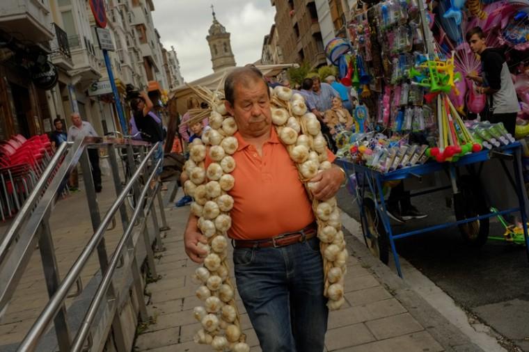 A man carries a strip of garlic during the garlic fair in Vitoria, northern Spain, on Monday. (Alvaro Barrientos/AP)