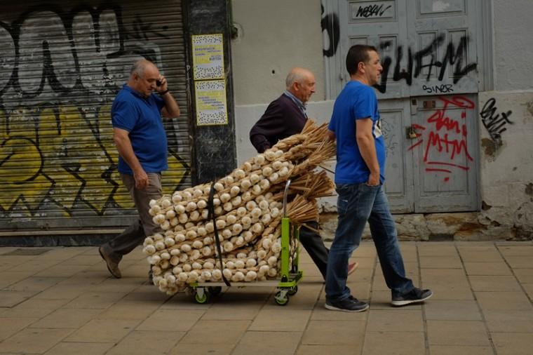 Men carry some strips of garlic during the garlic fair in Vitoria, northern Spain, on Monday. (Alvaro Barrientos/AP)