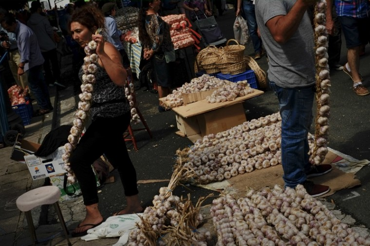 Sellers prepare strips of garlic during the garlic fair in Vitoria, northern Spain, on Monday, July 25, 2016. (Alvaro Barrientos/AP)