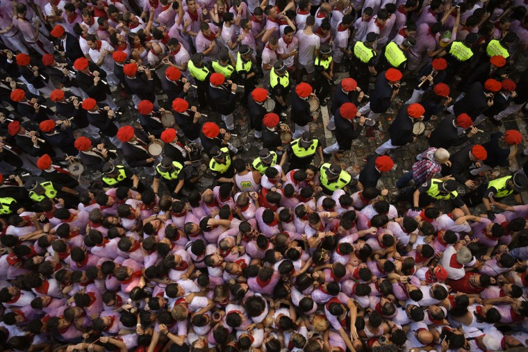 People celebrate beside ''Los Gaiteros '' musicians during the launch of the 'Chupinazo' rocket, to celebrate the official opening of the 2016 San Fermin Fiestas, in Pamplona, northern Spain, Wednesday, July 6, 2016. Revelers from around the world kick off the festival with a messy party in the Pamplona town square, one day before the first of eight days of the running of the bulls. (AP Photo/Alvaro Barrientos)