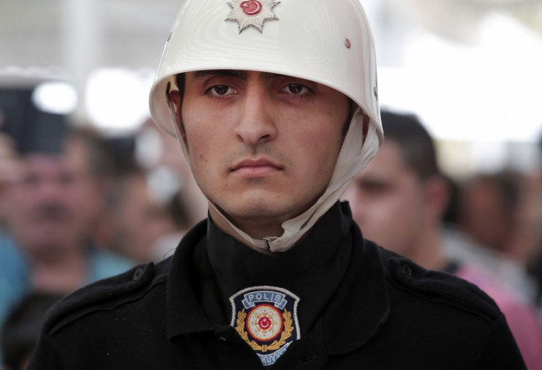 A Turkish police officer stands guard next to the coffin of Erol Ince, a police officer killed Friday during the failed military coup, during the funeral in Istanbul, Monday, July 18, 2016. Warplanes patrolled Turkey's skies overnight in a sign that authorities feared that the threat against President Recep Tayyip Erdogan's government was not yet over, despite official assurances that life has returned to normal after the failed coup. (AP Photo/Lefteris Pitarakis)