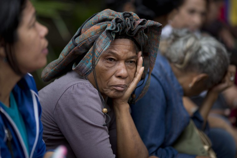 In this Tuesday, May 3, 2016 photo, Adelaida Ospina shades herself with her bag as she waits in line outside a supermarket to buy food in Caracas, Venezuela. The average Venezuelan spends 35 hours waiting to buy basic goods each month. Ospina said she arrived at 5:40am. (AP Photo/Ariana Cubillos)