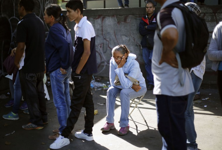 In this Friday, July 8, 2016 photo, a woman sleeps as she sits on the stool she brought with her, as she waits in line outside a supermarket to buy food in Caracas, Venezuela. All shoppers are limited to two units of whatever is on offer. (AP Photo/Ariana Cubillos)
