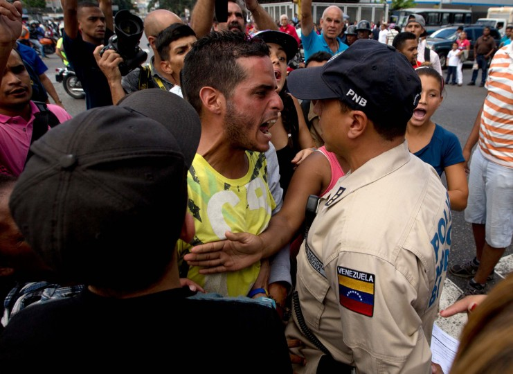 "In this Wednesday, June 8, 2016 file photo, a man waiting in line at a grocery store argues with a Bolivarian National Police officer as he and others wait for food to arrive to the store in Caracas, Venezuela. ""As the economy breaks down, life is telescoping to be just lines,"" said Datanalisis president Luis Vicente Leon. ""You have masses of people in the streets competing for scarce goods. You're inevitably going to get conflict, fights, tricks, you name it."" (AP Photo/Fernando Llano, File)"