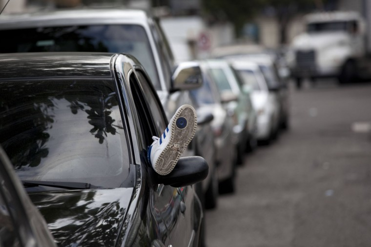 In this early Thursday, Aug. 6, 2015 file photo, a man rests in his car while in line outside the Duncan car battery store in Caracas, Venezuela. The number of batteries for sale is limited and changes daily while customers, some who are turned away, must bring their cars with them. (AP Photo/Ariana Cubillos, File)