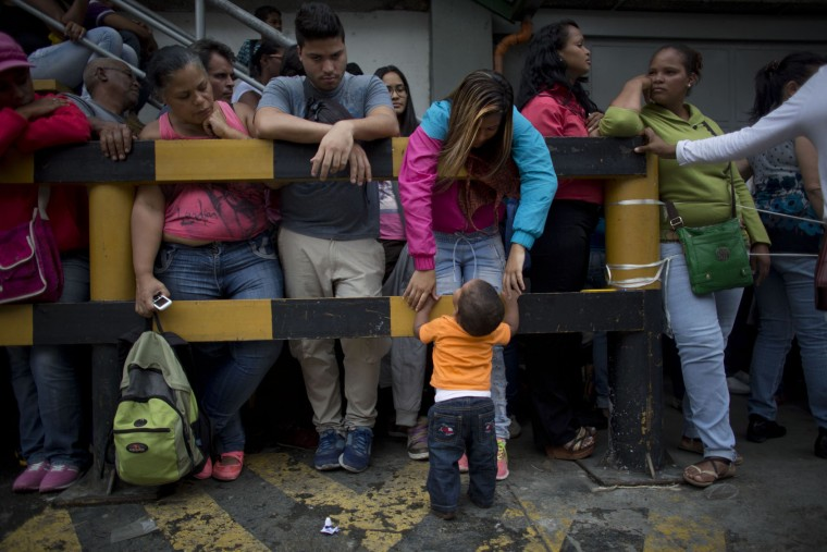 In this Tuesday, May 3, 2016, photo, sixteen-year-old Madeley Vasquez stands with her one-year-old son Joangel outside a supermarket as she waits to buy food in Caracas, Venezuela. Joangel was still experimenting with tentative steps when it came time for his mother to buy her two bags of rice and two packets of toilet paper. (AP Photo/Ariana Cubillos)