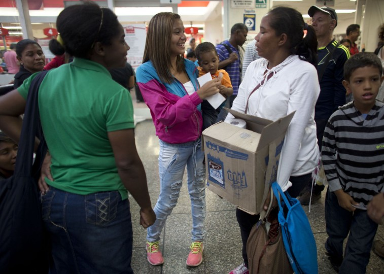 In this Tuesday, May 3, 2016 photo, sixteen-year-old Madeley Vasquez holds her one-year-old son Joangel as her mother Sorena carries a box of food out of the supermarket in Caracas, Venezuela, after spending over eight hours in line to buy one box of food. Sorena quit her job cleaning houses so she could spend more time waiting with her grandson and daughter to buy food. (AP Photo/Ariana Cubillos)
