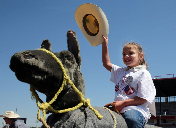 Caydence Brannaman raises her hat as she rides a horse during the Challenge Rodeo before the start of the 120th annual Cheyenne Frontier Days Rodeo at Frontier Park Arena Wednesday afternoon, July 27, 2016, in Cheyenne, Wyo. (Blaine McCartney/Wyoming Tribune Eagle via AP)