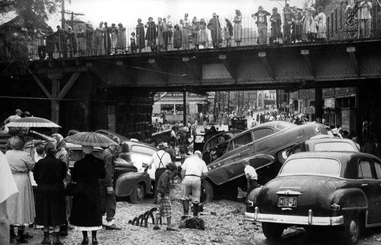 September 1, 1952-FLASH FLOOD DID THIS--Heavy rains brought by the hurricane produced a flash flood to Ellicott City which washed twenty-one cars down Main Street along with household furnishings and store merchandise. Here some of the cars are shown piled up near the depot yard at Main Street and Maryland Avenue. Photo by Sun photographer Frank A. Miller.