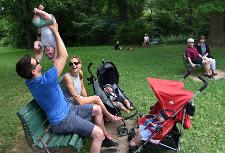 Thomas Hewitt Jr. hoists Finn during an outing to the park, as Kristin and Trip, center, watch with Thomas's parents, seated at the next bench. The third triplet, Ollie, is sleeping in the double stroller. (Amy Davis/Baltimore Sun)