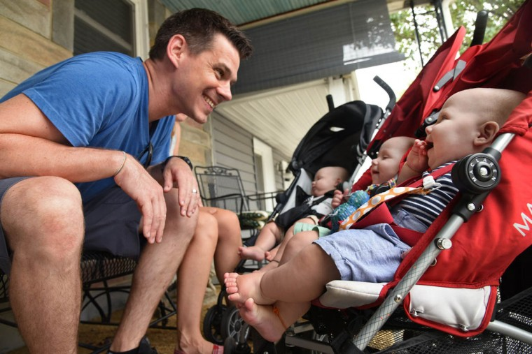 After returning from a walk, Thomas Hewitt Jr. responds to Finn, center, and Ollie, right, as they gaze at him from their double stroller. Trip, in the single stroller, is napping. (Amy Davis/Baltimore Sun)