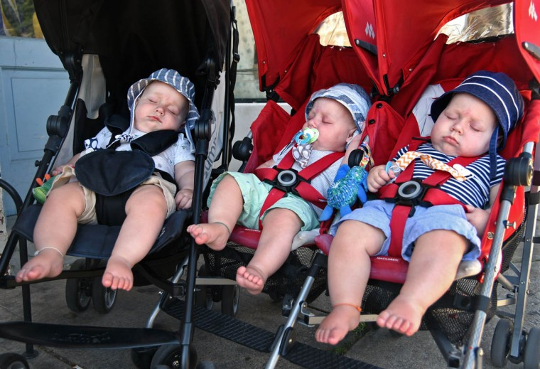 The Hewitt triplets, from left, Trip, Finn and Ollie, typically fall asleep during their morning stroller walk. While they nap, their parents get cold drinks at a Hampden cafe. The boys still wear different colored strings on their right ankles for identification. (Amy Davis/Baltimore Sun)
