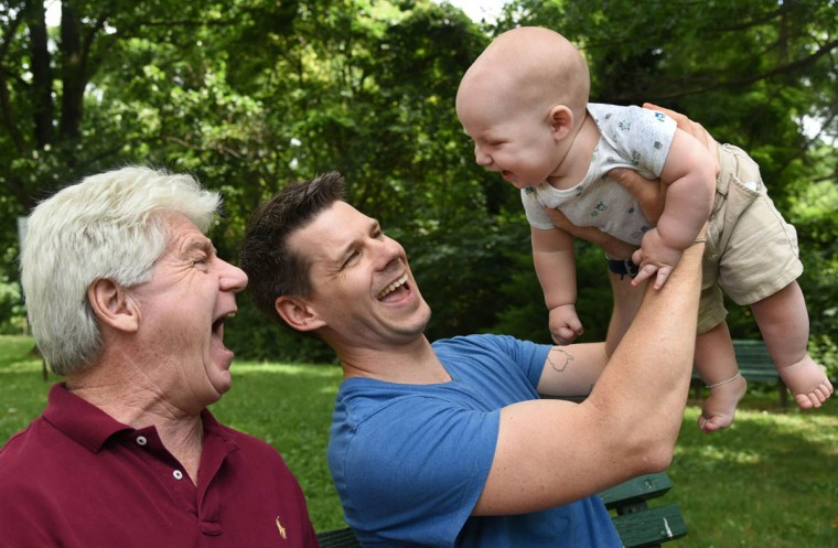 "Three generations share the same name: Thomas Hewitt Sr., left, of Ramsey, NJ, laughs with his grandson, Thomas ""Trip"" Hewitt III, who is held aloft by Thomas Hewitt Jr. (Amy Davis/Baltimore Sun)"