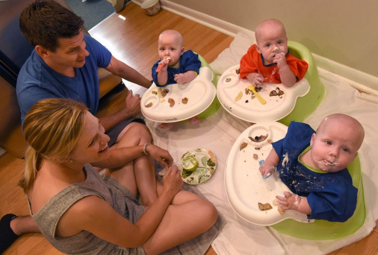 The triplets, from left, Trip, Finn and Ollie, ensconced in oversized smocks, enjoy exploring solid foods with the help of their watchful parents. (Amy Davis/Baltimore Sun)