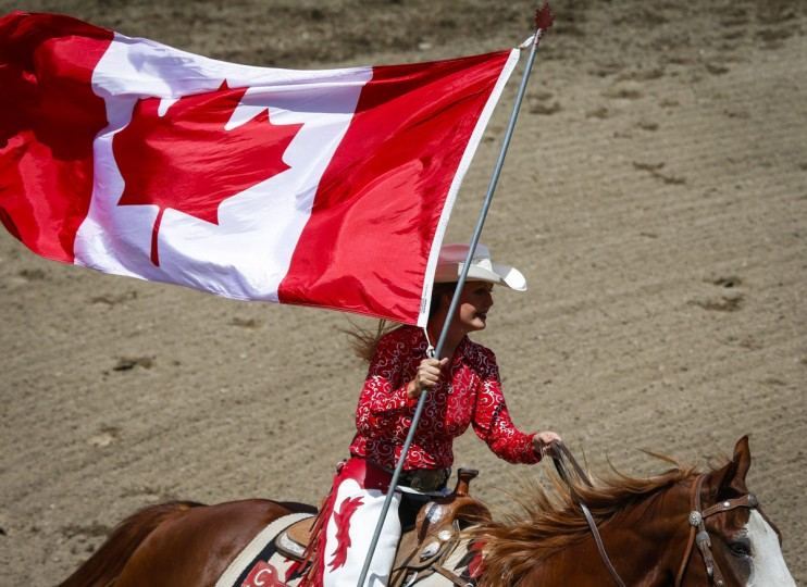 A rodeo queen rides with the Canadian flag during the national anthem before the Calgary Stampede in Calgary, Alberta, Sunday, July 10, 2016. (Jeff McIntosh/The Canadian Press via AP)