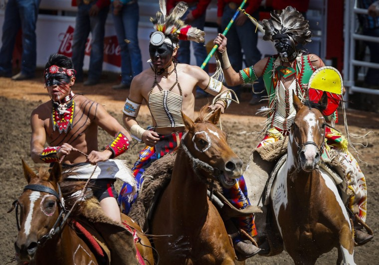 Native riders gallop around the infield as part of the opening ceremonies before rodeo action during the Calgary Stampede in Calgary, Alberta, Sunday, July 10, 2016. (Jeff McIntosh/The Canadian Press via AP)