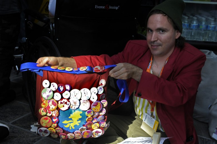 """Josh Van from Albuquerque, New Mexico shows off his bag covered with buttons and pins he's collected at other conventions and on the Internet. This is Van's third BronyCon convention. """"I come back for the vendors, people, and panels. It's a really good experience. I met a lot of friends here."""" BronyCon is the world's largest My Little Pony: Friendship is Magic convention. Held at the Baltimore Convention Center, BronyCon features panels, meet-ups, activities, and cosplay. (Caitlin Faw/Baltimore Sun staff)"""