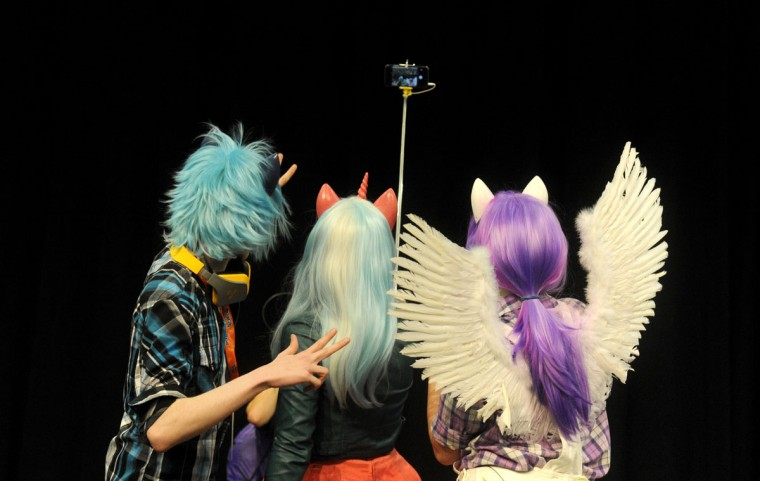 Three presenters in cosplay take a group selfie during the Opening Ceremonies that took place in the Maine Event's Hall. BronyCon is the world's largest My Little Pony: Friendship is Magic convention. Held at the Baltimore Convention Center, BronyCon features panels, meet-ups, activities, and cosplay. (Caitlin Faw/Baltimore Sun staff)
