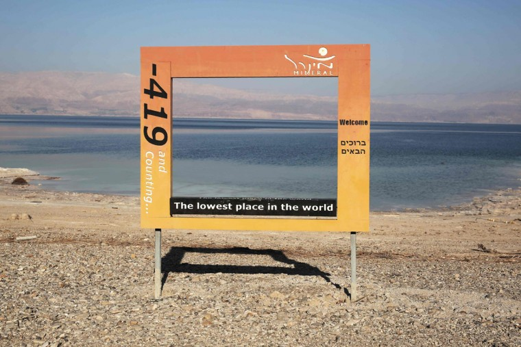 "A general view shows a large frame for visitors to take pictures at ""the lowest place in the world"" at a beach on the shore of the Dead Sea after is was abandoned following the appearance of sinkholes in the tourist resort of Mineral in the West Bank on July 11, 2016. (MENAHEM KAHANA/AFP/Getty Images)"