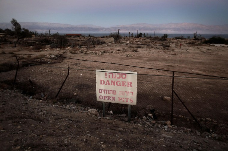 A general view shows a poster warning visitors of sinkholes in Israel's abandoned tourist resort of Ein Gedi on the shore of the Dead Sea on July 11, 2016. (MENAHEM KAHANA/AFP/Getty Images)