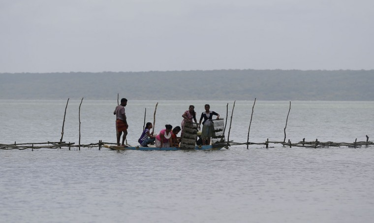 In this July 18, 2016 photo, Sri Lankan women engaged in small scale fishing, inspect their shellfish nest initiated by a micro finance loan, in a lagoon in Kalpitiya, about 130 kilometers (81 miles) north of Colombo, Sri Lanka. Sri Lanka's government and environmentalists are working to protect tens of thousands of acres of mangrove forests -- the seawater-tolerant trees that help protect and build landmasses, better absorb carbon from the environment mitigating effects of global warming and reducing impact of natural disasters like tsunamis. Authorities have identified about 37,000 acres (15,000 hectares) of mangrove forests in Sri Lanka that are earmarked for preservation. (AP Photo/Eranga Jayawardena)