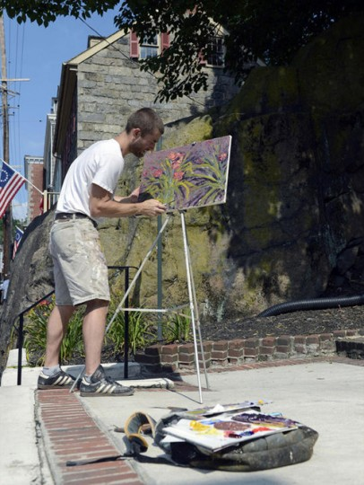 Chris Nelson of Cumberland paints a garden of flowers along Main Street during the Quick Draw competition on July 9. (Nicole Munchel/Baltimore Sun Media Group)