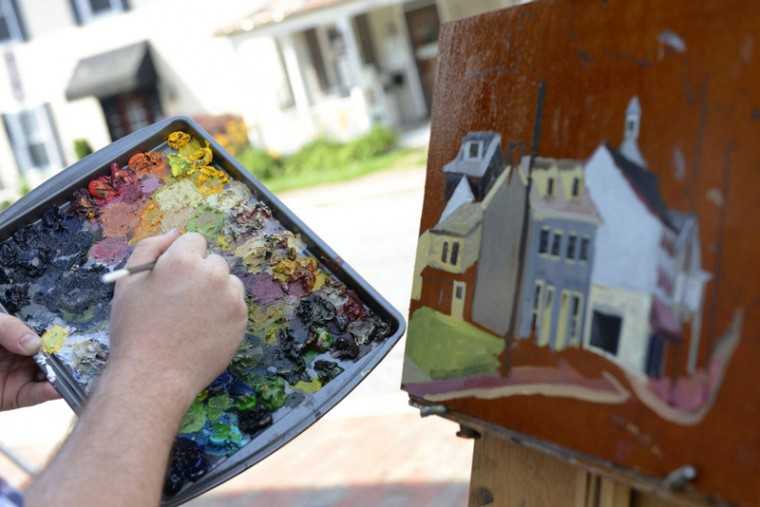 Alex Wissel of Catonsville uses oil on board for his Quick Draw piece July 9 during the Paint It! Ellicott City plein air event. (Nicole Munchel/Baltimore Sun Media Group)