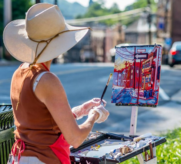 Caroline Jasper paints a scene from the top of Main Street. (Raymond Urena/via Howard County Arts Council)