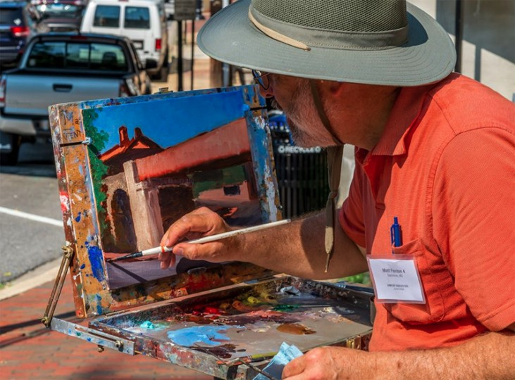 A plein air artist paints in the heat. Paint It! Ellicott City, presented by  the Howard County Arts Council, Howard County Tourism & Promotion, Mat About You Gallery & Framing, Ellicott City Partnership, and the Howard County Public School System, was held three weekends before the flood. (Raymond Urena/via Howard County Arts Council)