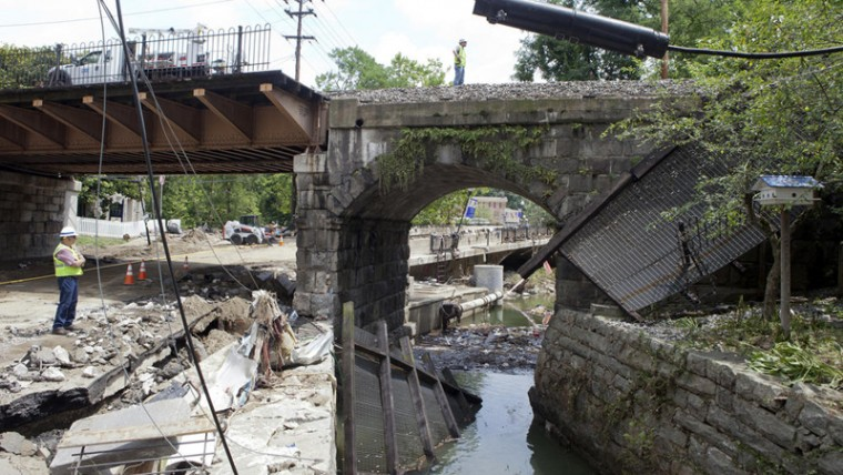 A man surveys damage near the railroad bridge over Main Street. (Jen Rynda/Baltimore Sun Media Group)