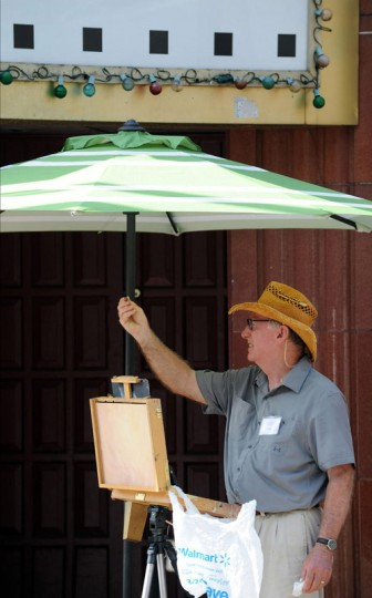 Raymond Ewing of Swan Point brought an umbrella to keep cool during Paint It! Ellicott City's Quick Draw competition on July 9. (Nicole Munchel/Baltimore Sun Media Group)