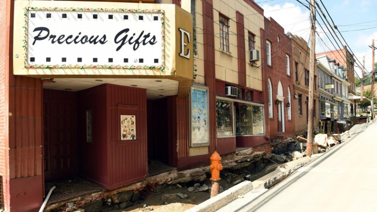 Precious Gifts, the collectibles store Ewing was painting in front of, is seen just over three weeks later on Aug. 3, an entire block of sidewalk washed away. (Brian Krista/Baltimore Sun Media Group)