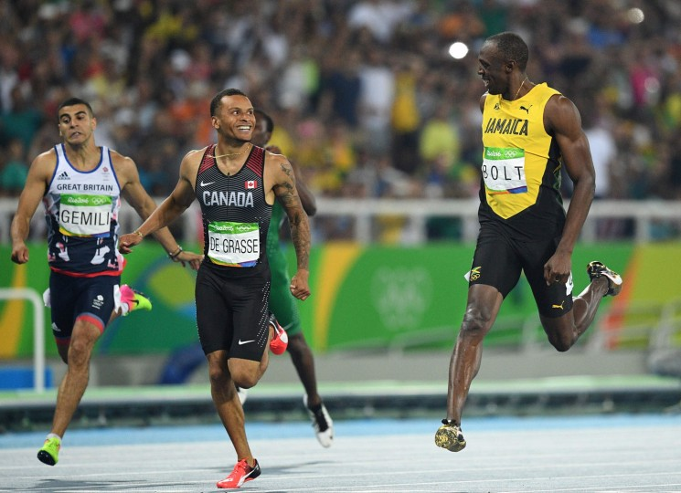 Jamaica's Usain Bolt (R) shares a laugh with de Canada's Andre De Grasse after their Men's 200m Semifinal during the athletics event at the Rio 2016 Olympic Games at the Olympic Stadium in Rio de Janeiro on August 17, 2016. (Johannes Eisele/AFP/Getty Images)