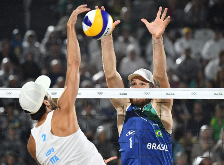 Italy's Daniele Lupo spikes the ball during the men's beach volleyball final match between Italy and Brazil at the Beach Volley Arena in Rio de Janeiro late on August 18, 2016, for the Rio 2016 Olympic Games. (Leon Neal/AFP/Getty Images)