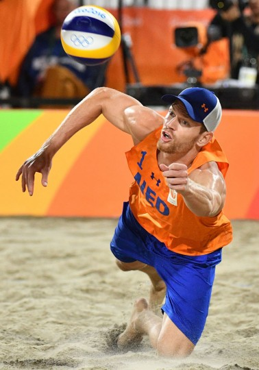 Alexander Brouwer of the Netherlands dives for the ball during the men's beach volleyball bronze medal match between Russia and the Netherlands at the Beach Volley Arena in Rio de Janeiro on August 18, 2016, for the Rio 2016 Olympic Games. (Leon Neal/AFP/Getty Images)