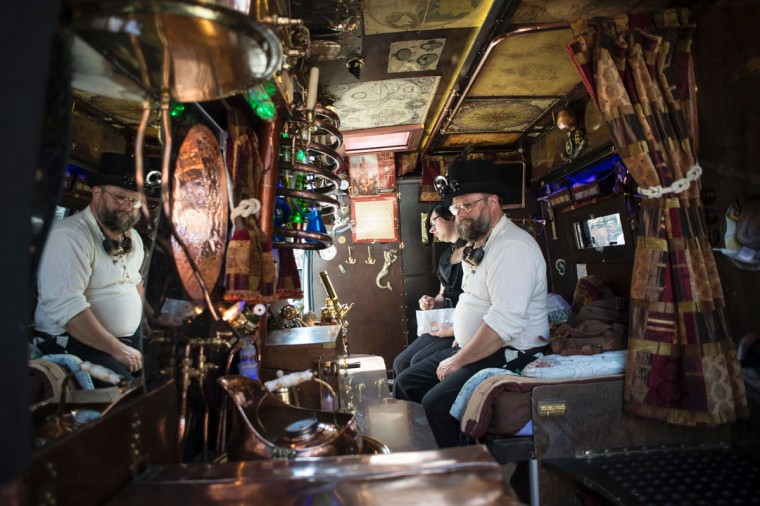 enthusiasts sit in their customised motorhome as they attend the first day of 'The Asylum Steampunk Festival' in Lincoln, northern England on August 26, 2016.The four-day alternative lifestyle festival is the largest and longest running steampunk festival in the World; combining art, literature, music, fashion and comedy. Steampunk is a subgenre of science fiction or science fantasy that incorporates technology and aesthetic designs inspired by 19th-century industrial steam-powered machinery. / (AFP Photo/Oli Scarff)