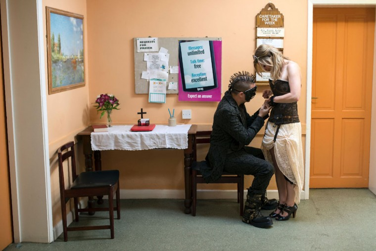 Steampunk enthusiasts fix their attire in a church hall on the first day of 'The Asylum Steampunk Festival' in Lincoln, northern England on August 26, 2016. The four-day alternative lifestyle festival is the largest and longest running steampunk festival in the World; combining art, literature, music, fashion and comedy. Steampunk is a subgenre of science fiction or science fantasy that incorporates technology and aesthetic designs inspired by 19th-century industrial steam-powered machinery. / (AFP Photo/Oli Scarff)